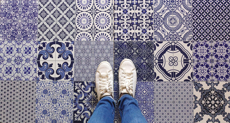 Selfie of feet with sneaker shoes on art pattern tiles floor bac