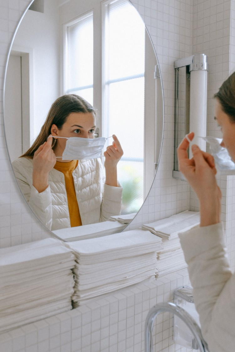 Best Face Masks - Woman putting a face mask in front of the mirror