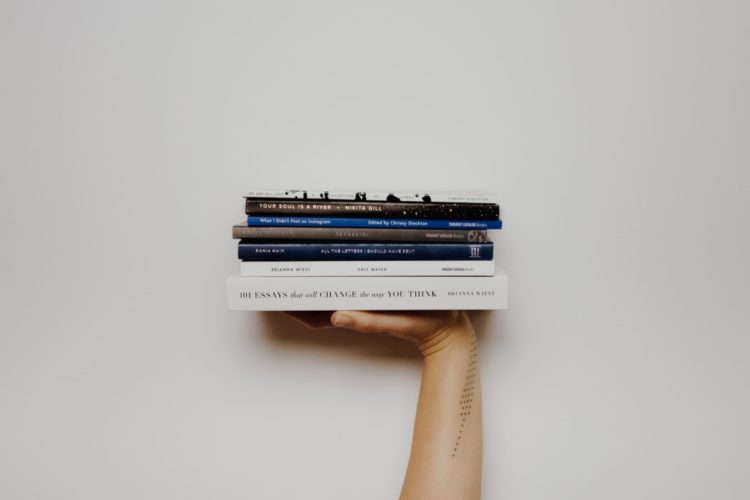 A hand holding 6 books