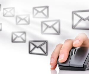 Email icons around female hand using computer mouse