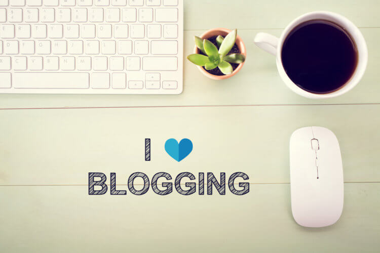 I Love Blogging concept with workstation on a light green wooden desk