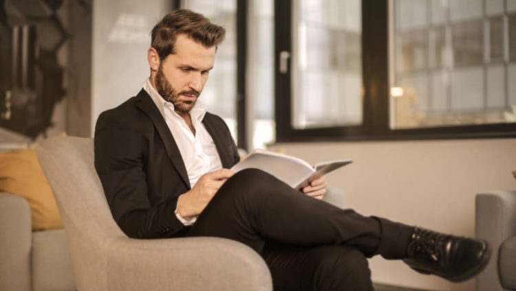 Man in Black Suit Reading Fashion Magazine