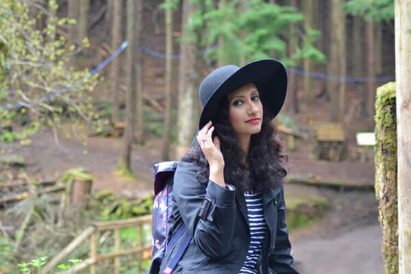 natasha kundi sitting blue jacket hat