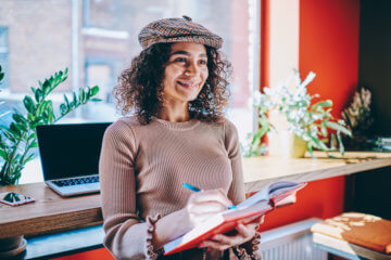 female author looking away thinking about article holding textbook in hands
